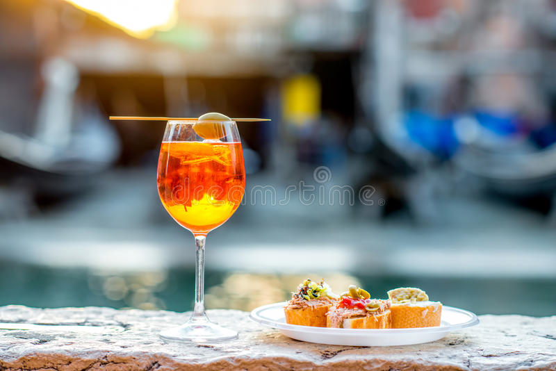 Spritz Aperol with cicchetti. Spritz Aperol drink with venetian traditional snacks cicchetti on the water chanal background in Venice. Traditioanal italian royalty free stock images
