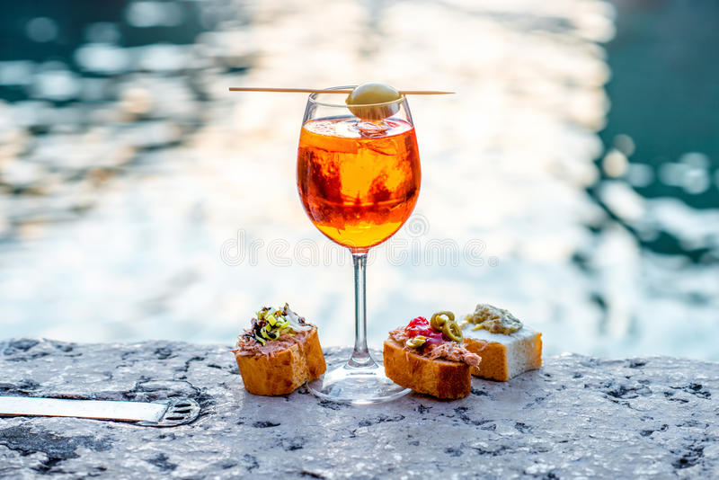 Spritz Aperol with cicchetti. Spritz Aperol drink with venetian traditional snacks cicchetti on the water chanal background in Venice. Traditioanal italian royalty free stock photos