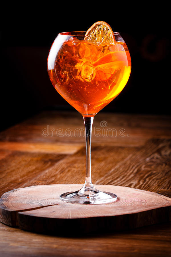 Spritz Aperol cocktail in a glass glass. On a wooden board dark background royalty free stock photo