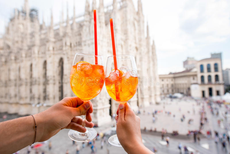 Spritz aperol drink in Milan. Clinking glasses of spritz aperol drink on the main square with Duomo cathedral on the background in Milan city stock images