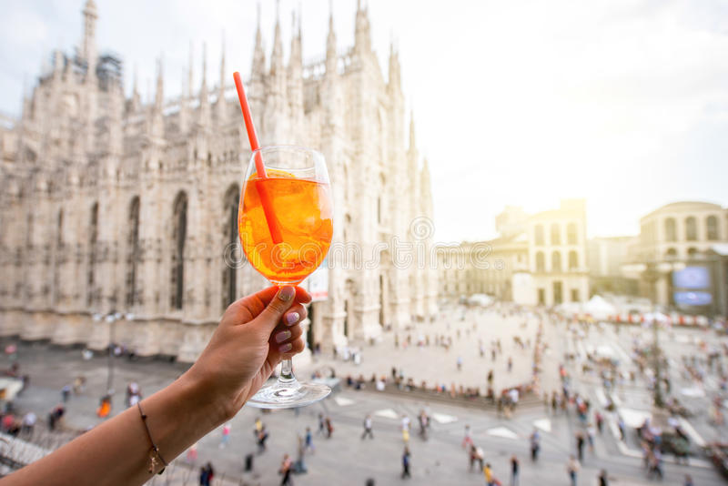 Spritz aperol drink in Milan. Holding a glass of spritz aperol drink on the main square with Duomo cathedral on the background in Milan city stock photo