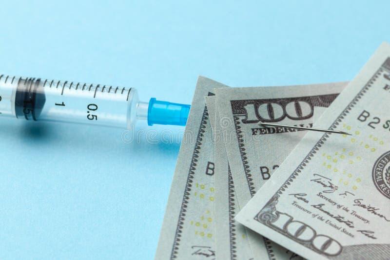Spritze und Papierdollar festgesteckt zur Nadel auf blauem Hintergrund Teure Krankenversicherung stockbilder