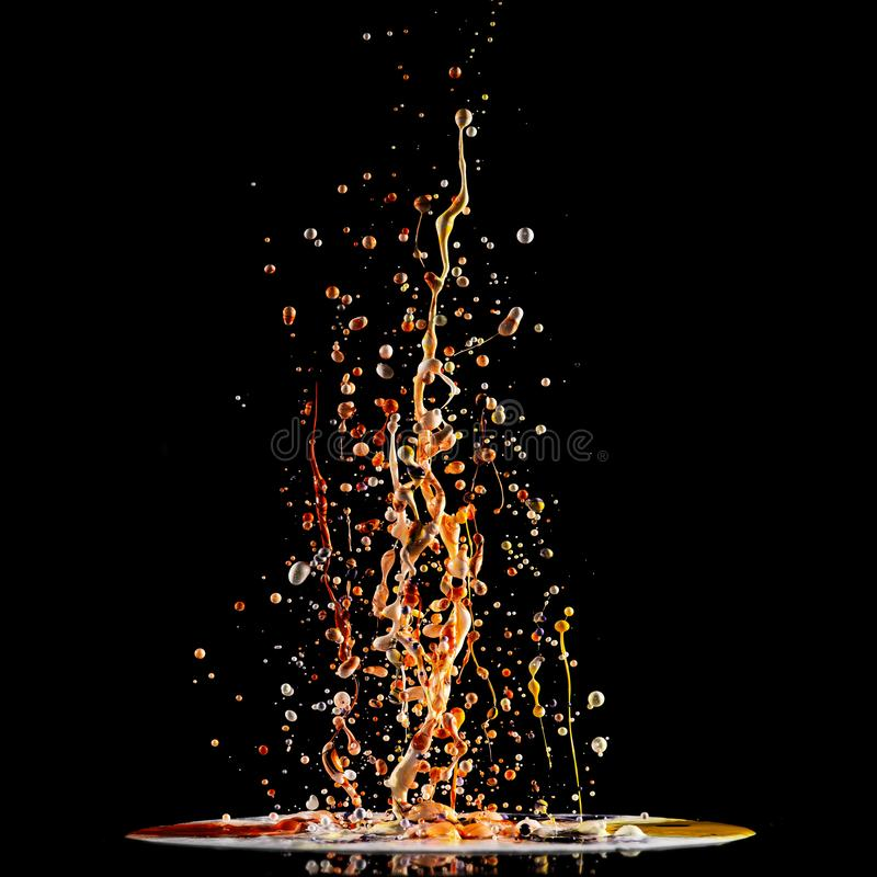 Spritzen der Acrylfarbe, mehrfarbige Farbenexplosion, abstrakter Hintergrund auf Schwarzem stockbild