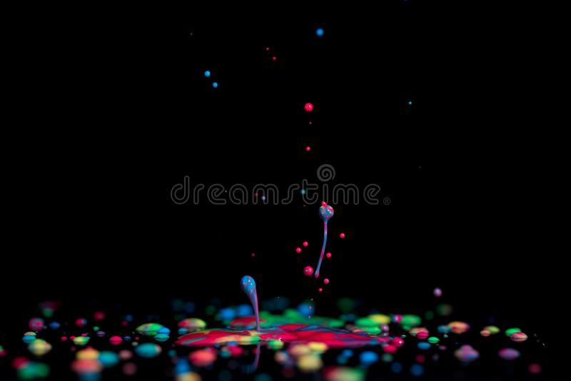 Spritzen der bunten flüssigen Farbe auf einem schwarzen Hintergrundfarbe spla stockfotografie