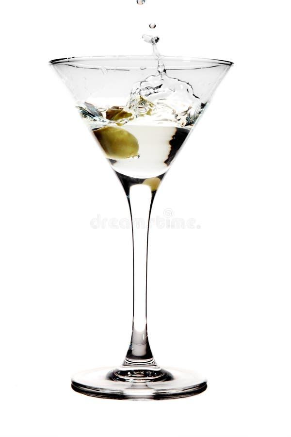Spritzen der Olive in ein Martini-Glas stockbild