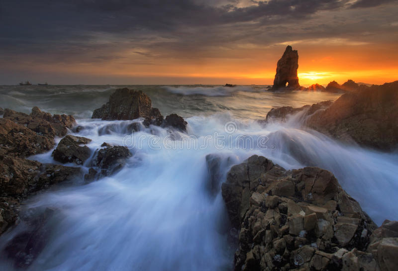 Spritzen der Welle mit schönem Sonnenuntergang lizenzfreie stockbilder
