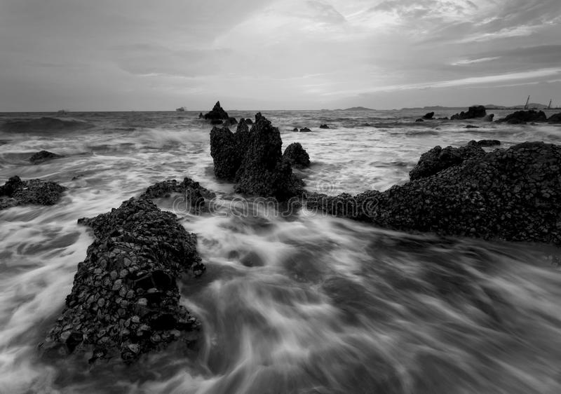 Spritzen der Welle mit schönem Sonnenuntergang in Schwarzweiss lizenzfreie stockfotos