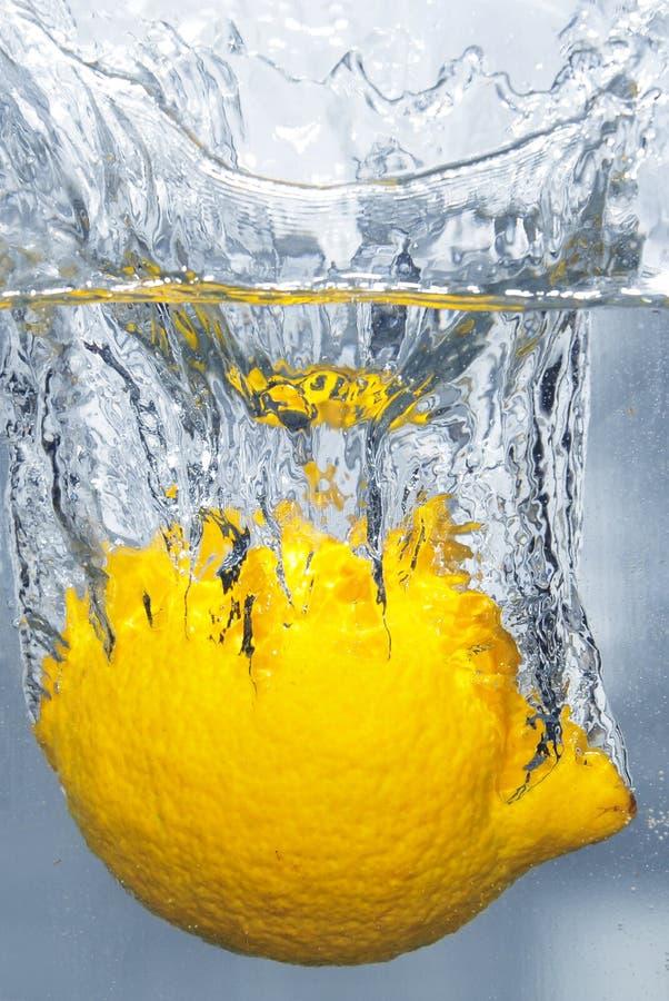 Spritzen der Zitrone in ein Wasser lizenzfreie stockfotos