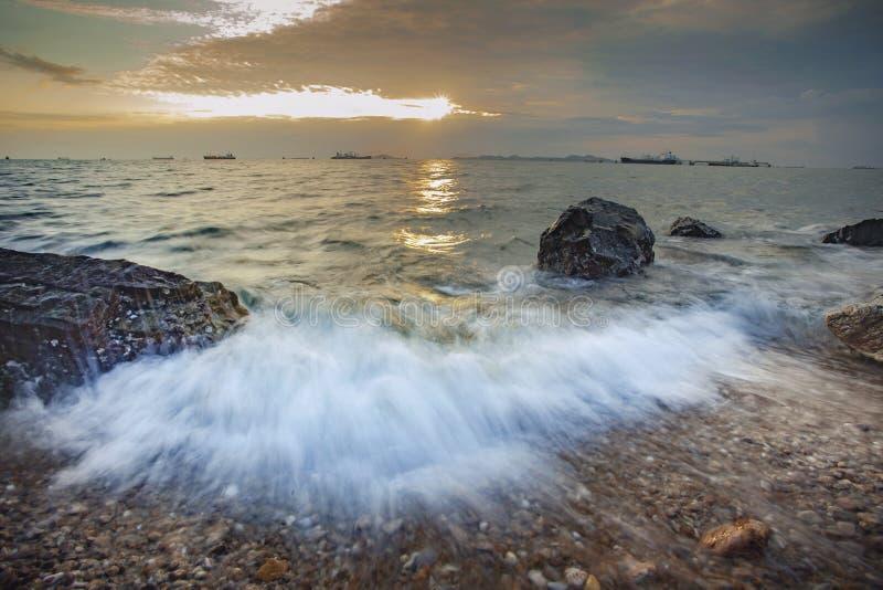 Spritzen des Meerwassers und des schönen Sonnenunterganghimmels an laem chabang cho stockfotografie
