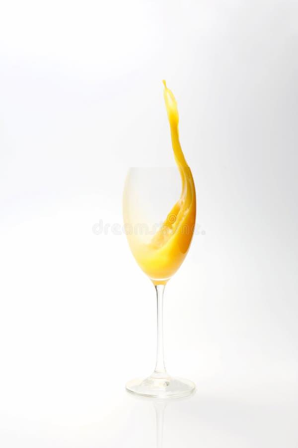 Spritzen des Orangensaftes im Glas auf weißem Hintergrund lizenzfreie stockbilder