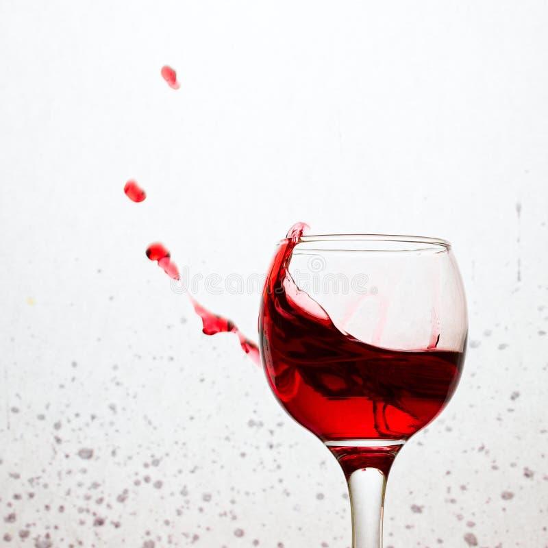 Spritzen des Rotweins auf einem grauen Hintergrund mit Flecken von einem Bewässerungsgetränk des Munds stockfoto