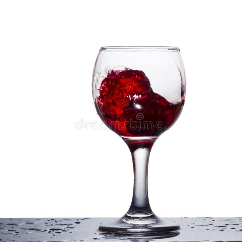Spritzen des Rotweins in einem Glas ähnlich einer Explosion stockbild