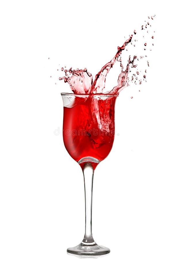 Spritzen des Rotweins im Becher lizenzfreie stockfotografie
