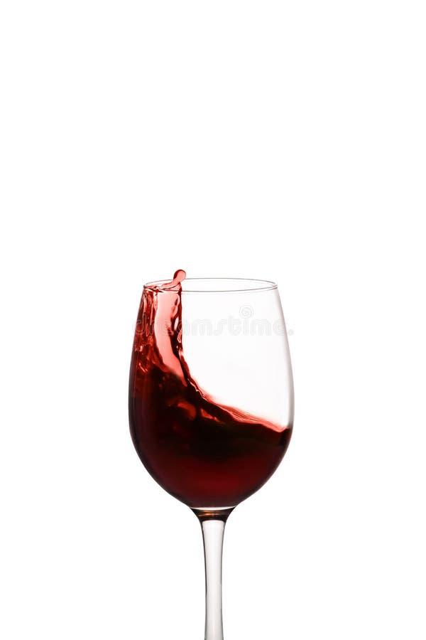 Spritzen des Rotweins im Glas lizenzfreie stockbilder