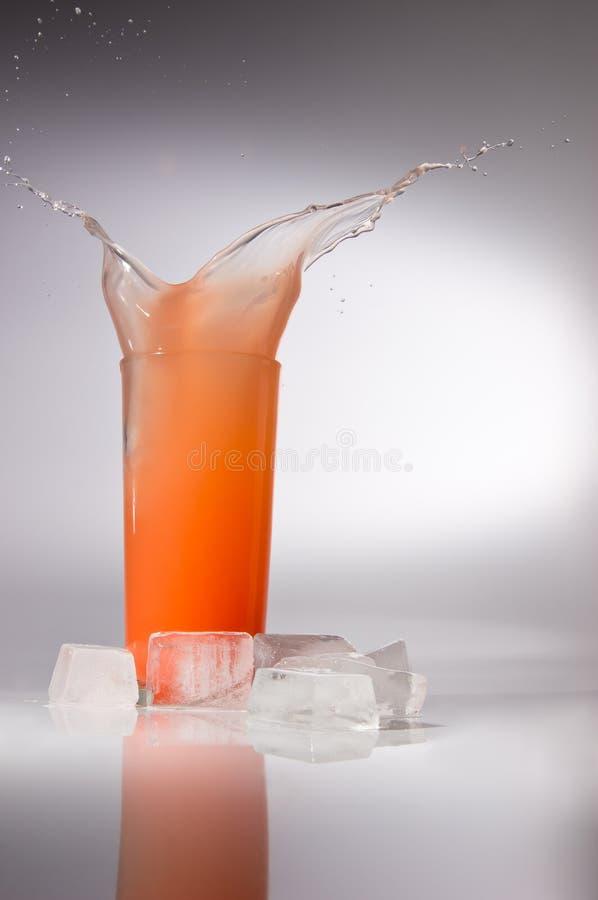 Spritzen des Safts im Glas mit Eis lizenzfreie stockfotos