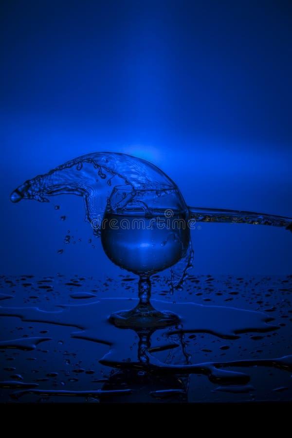 Spritzen des Wassers im Weinglas auf einem blauen Hintergrund lizenzfreies stockbild
