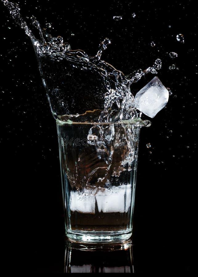 Spritzen des Wassers mit einem Eiswürfel in einem Glas lizenzfreie stockfotos