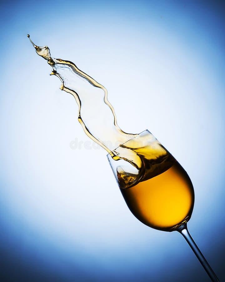 Spritzen des Weißweins vom Becher lizenzfreie stockfotografie