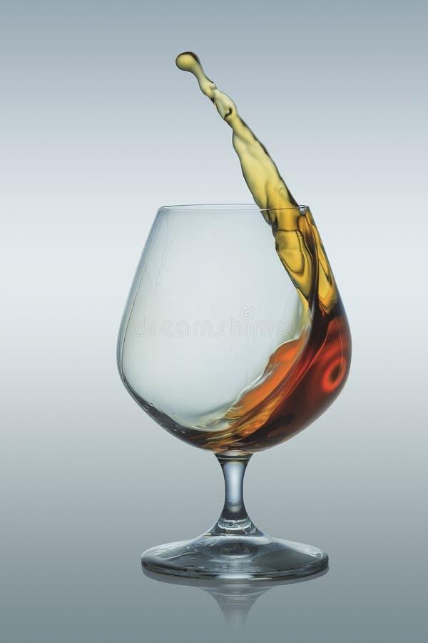 Spritzen des Weinbrands im Glas lizenzfreie stockfotografie