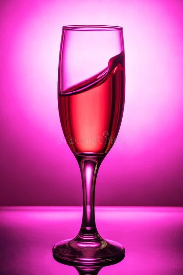 Spritzen des Weins in einem Glasbecher lizenzfreie stockfotos