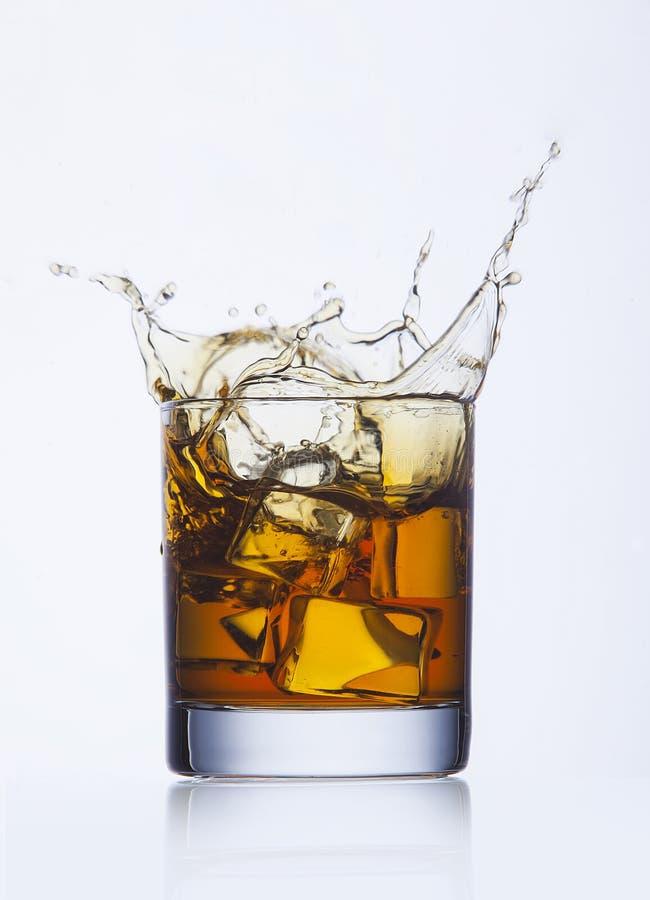 Spritzen des Whiskys im Glas stockfotografie