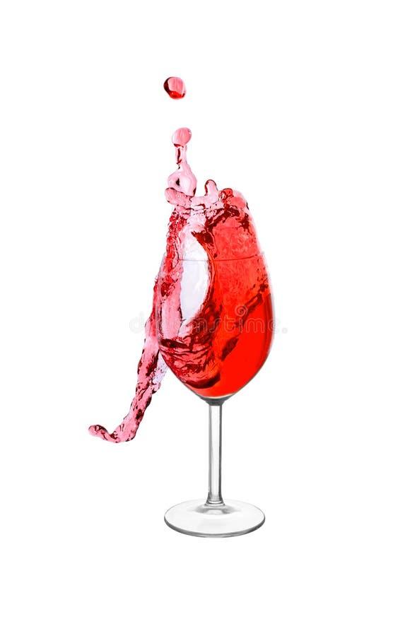 Spritzen in einem Rotweinglas stockfotografie