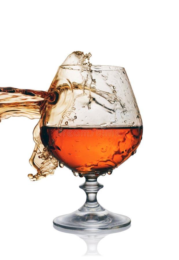 Spritzen im Glas des Kognaks stockbild