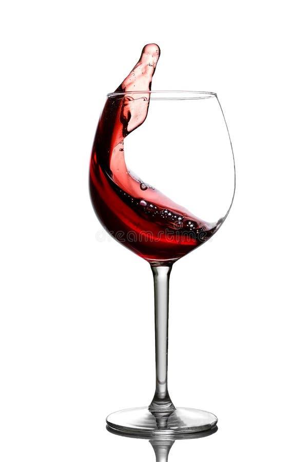 Spritzen im Rotwein in einem Glas stockbild