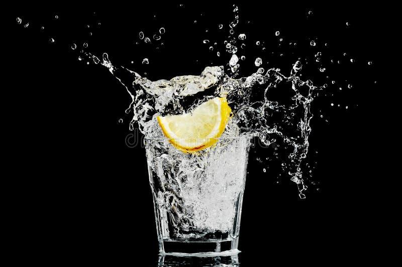 Spritzen Sie in einem Glas mit Zitrone und Eis auf einem schwarzen Ba stockfoto