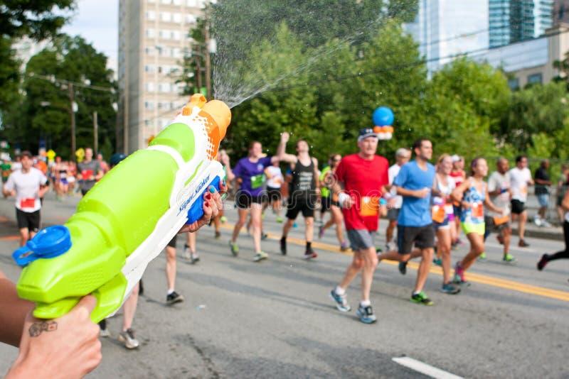 Spritzen Sie Gewehr tränkt Läufer in Straßenrennen Atlantas Peachtree stockfoto