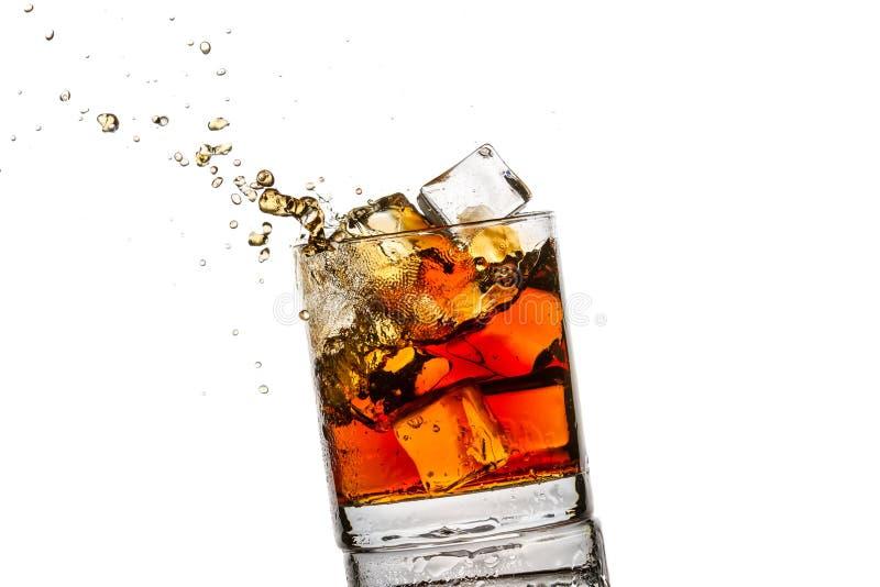 Spritzen Sie im Glas mit Whisky- und Eiswürfeln stockfoto