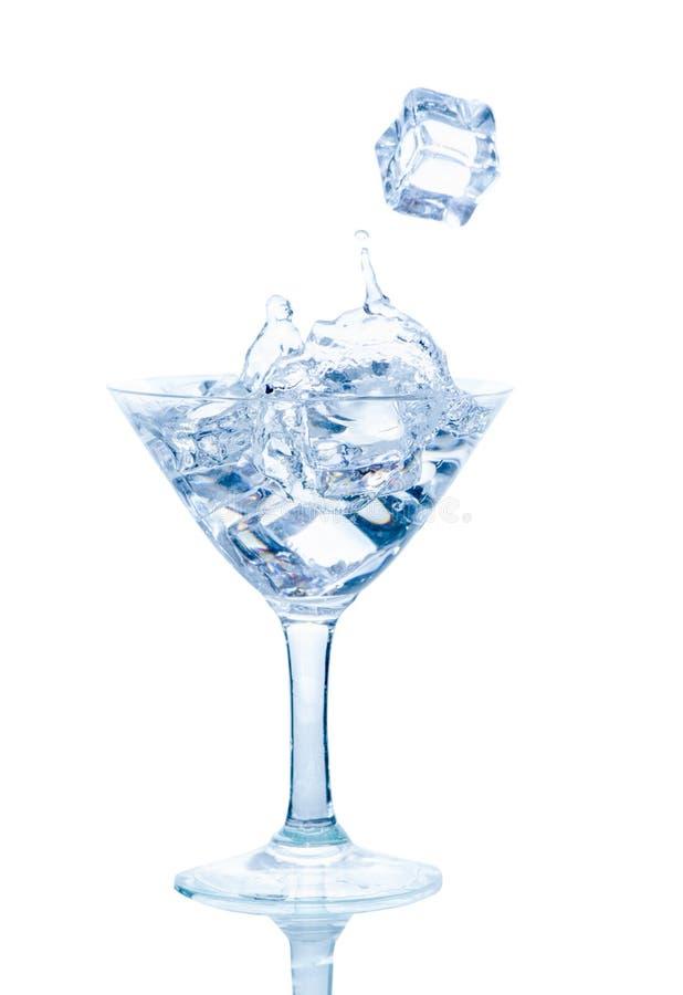 Spritzen Sie vom Eiswürfel in einem Weinglas Wasser lizenzfreie stockfotografie