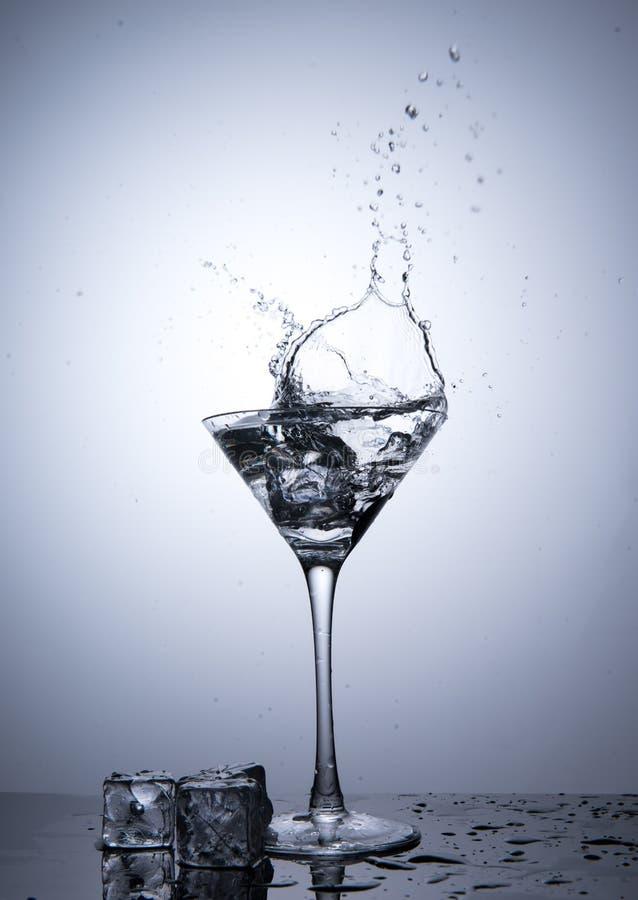 Spritzen Sie vom Eiswürfel in lokalisiertem Martini-Glas stockfoto