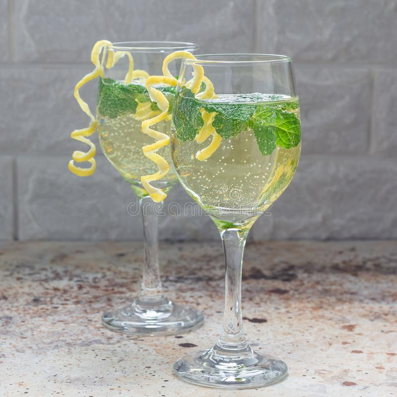 Spritzer cocktail with white wine, mint and ice, decorated with spiral lemon zest, square format royalty free stock photography