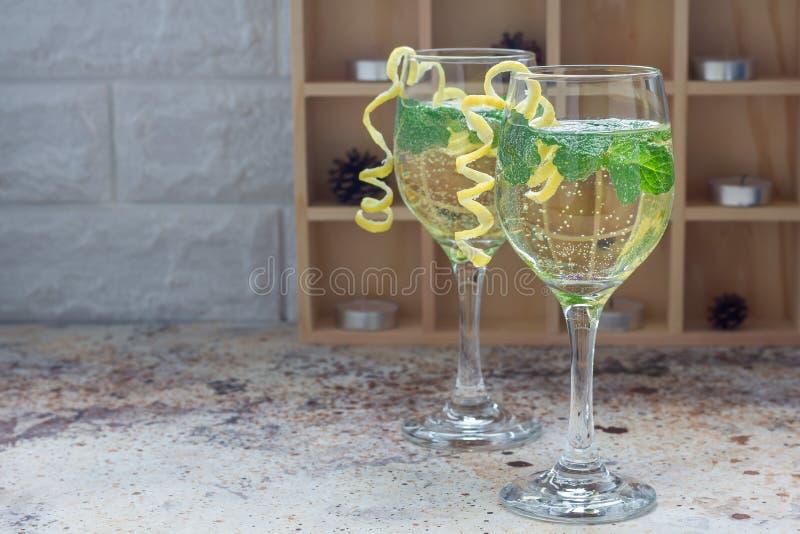 Spritzercocktail met wit die wijn, munt en ijs, met spiraalvormige citroenschil wordt verfraaid, exemplaarruimte stock fotografie