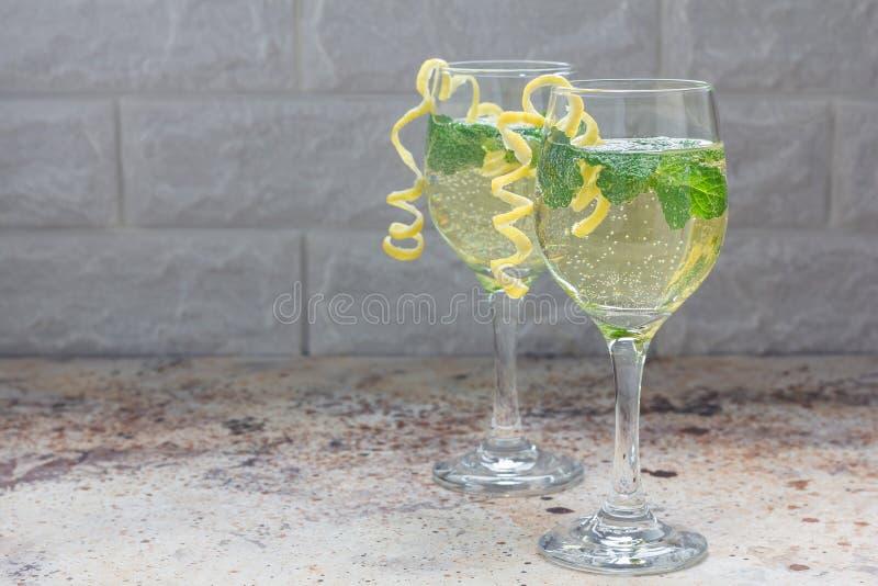Spritzercocktail met wit die wijn, munt en ijs, met spiraalvormige citroenschil wordt verfraaid, exemplaarruimte stock foto's