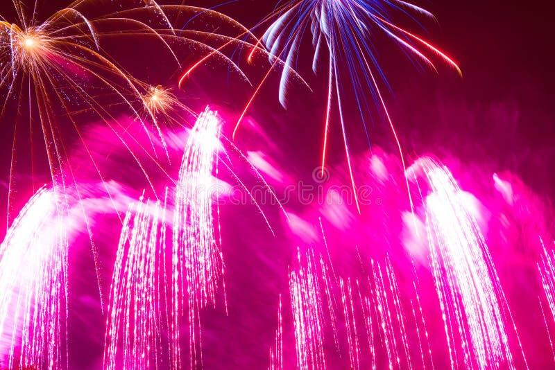 spritzt von den rosa hellen schönen Feuerwerken im nächtlichen Himmel an lizenzfreie stockfotografie