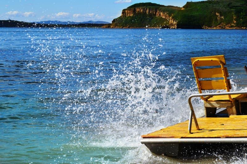 Spritzt von zusammenstoßenden Wellen auf der Seite des gelben Katamarans und steht auf dem Strand des touristischen Lagers lizenzfreies stockfoto