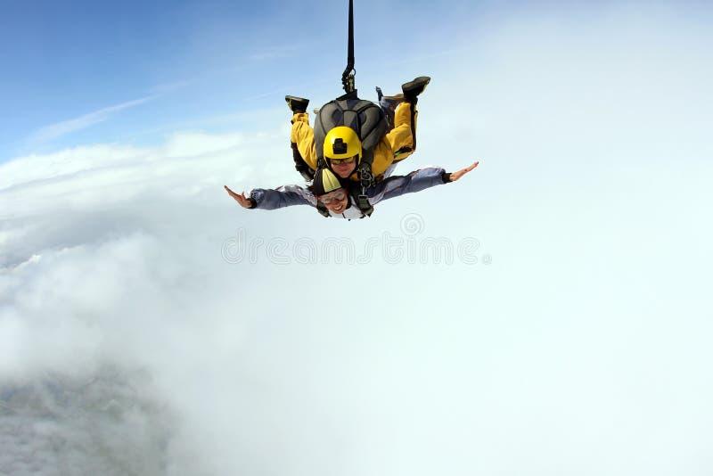 Sprong achter elkaar Skydiving in de blauwe hemel stock foto