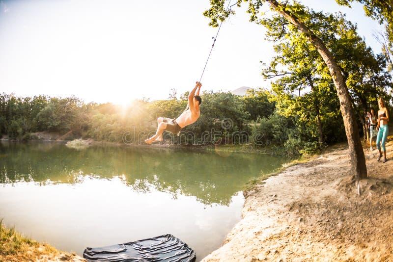 Sprong in het water Een mens rust op de aard Een schommeling van een kabel en een stok Actieve recreatie in aard De vrienden hebb royalty-vrije stock foto's