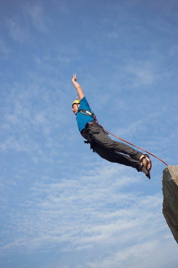 Sprong van de klip met een kabel stock fotografie