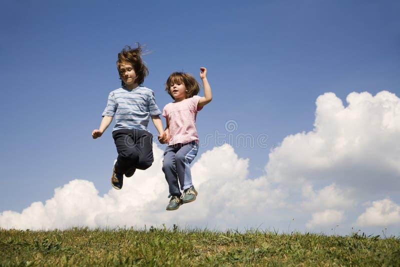 Sprong van kinderen en de hemel stock foto's