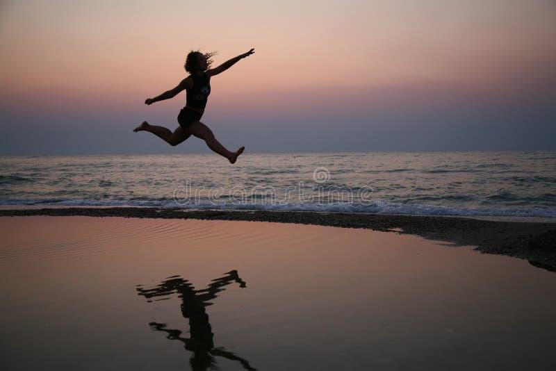 Sprongen op strand op zonsondergang stock foto