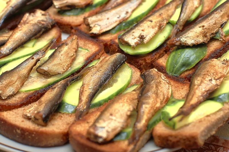 Sprotten met komkommerplakken op geroosterd brood, close-up royalty-vrije stock afbeelding