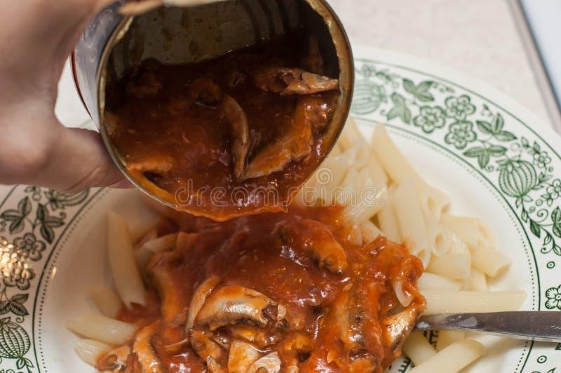 Sprotten in tomatensaus toevoegen aan deegwaren voor een betere eetlust stock afbeelding