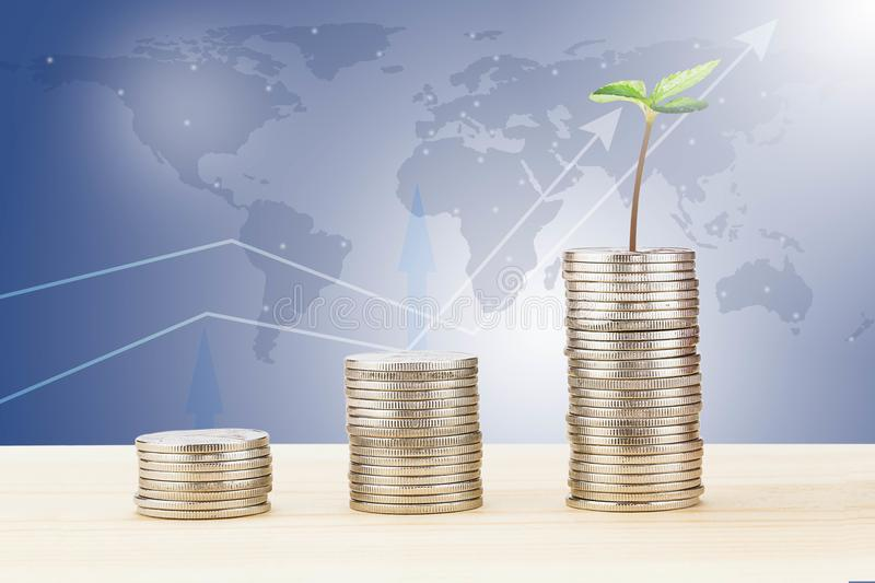 Sprout growing from stack of coins on wooden desk on blurred world map and line graph background. Business financial concept royalty free stock image