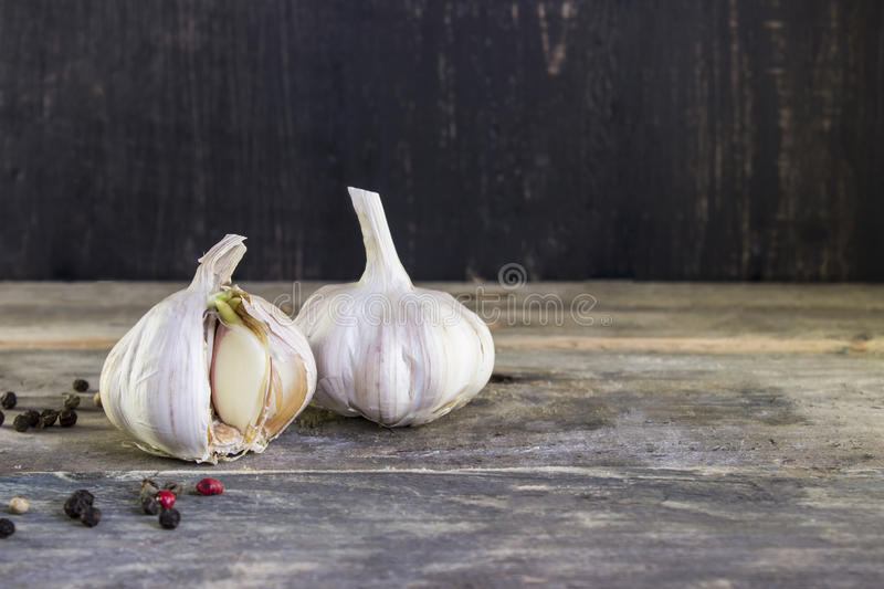 Sprouted garlic with pepper on a wooden table.  stock image
