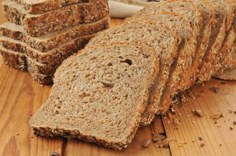 Sprouted grain and seed bread. A sliced loaf of sprouted grain and seed bread on a cutting board royalty free stock image