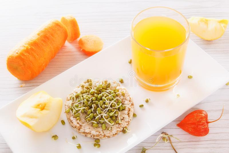 Sprouted grains, puffed, fresh juice, apples and vegetables. Useful breakfast from natural products royalty free stock image