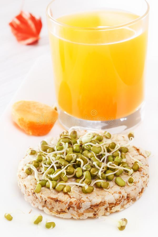 Sprouted grains on puffed wheat cakef, fresh juice, carrots. Healthy food from natural products royalty free stock images
